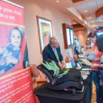 exhibitor discussing child safety seat