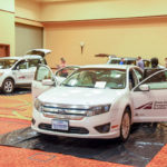 Cars inside an exhibit hall with people